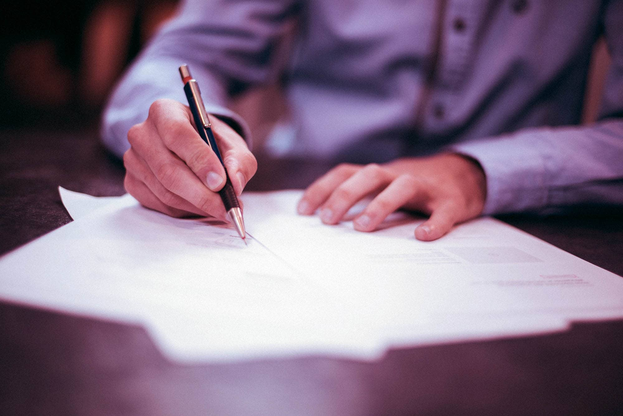 Photo of man signing a legal document. (photo: unsplash)